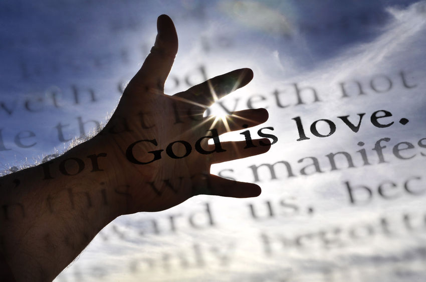 Hand over scripture showing our Creator God is a God of love