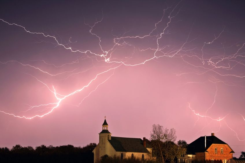Laodicean church depicted under storm clouds with bright lightning crashing above