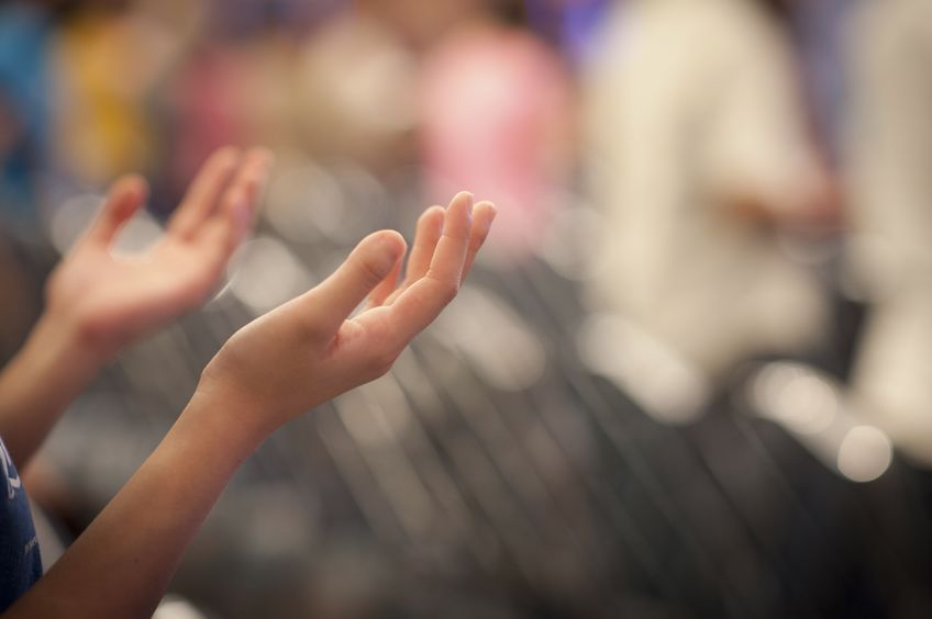 Hands raised worshiping in church?