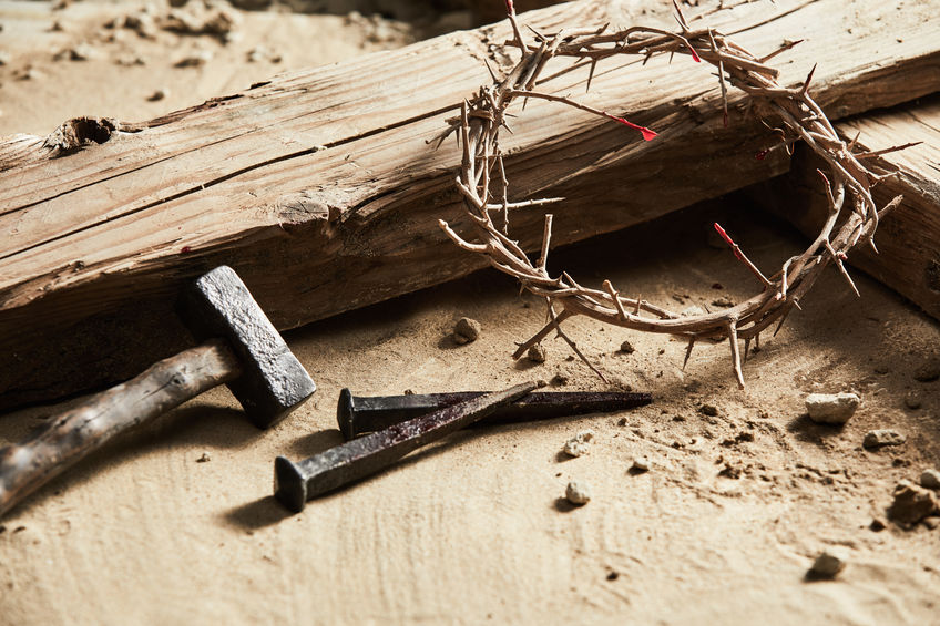 Someone died for you - crown of thorns and nail lying by a wooden cross