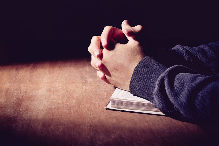 Hands on Bible praying, self reflection, looking at ourselves